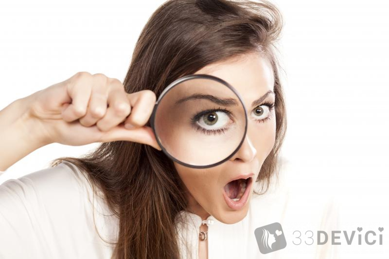 shocked-young-woman-looking-through-a-magnifying-glass