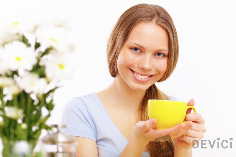 Улыбающаяся молодая блондинка пьет чай