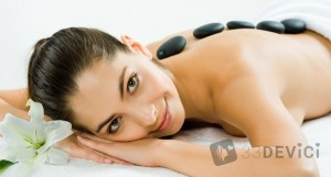 Photo of a beautiful smiling woman lying with spa stones on her back and looking at camera with white lily near by